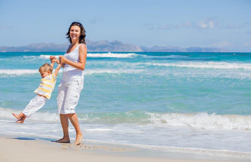 Moder och son som har gyckel på strand fotografering för bildbyråer