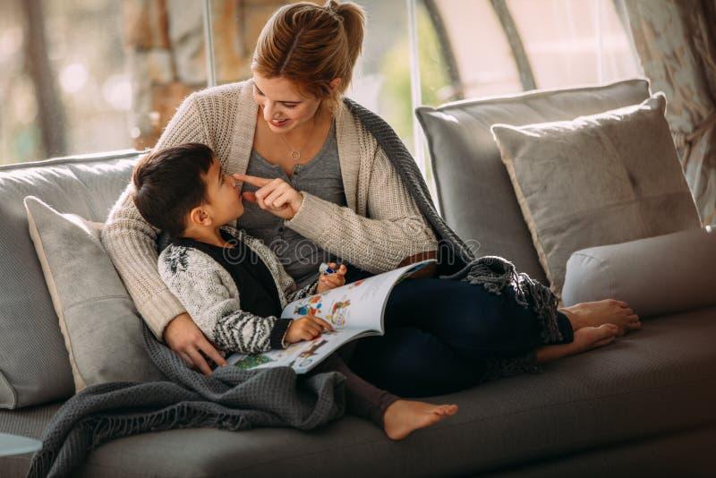 Moder och son som har roligt, medan läsa en sagobok fotografering för bildbyråer