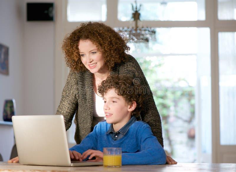 Moder och son som hemma använder datoren arkivbild