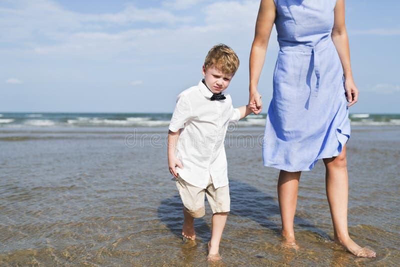 Moder och son som kyler på stranden royaltyfria bilder