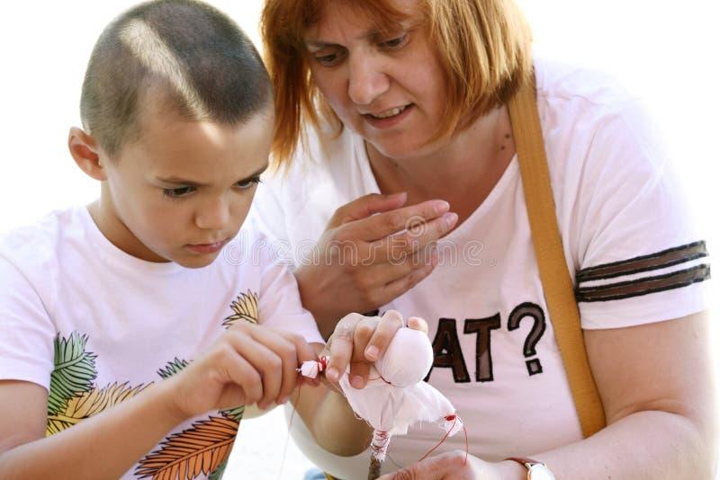 Moder och son som lär att göra hantverkobjekt arkivfoton