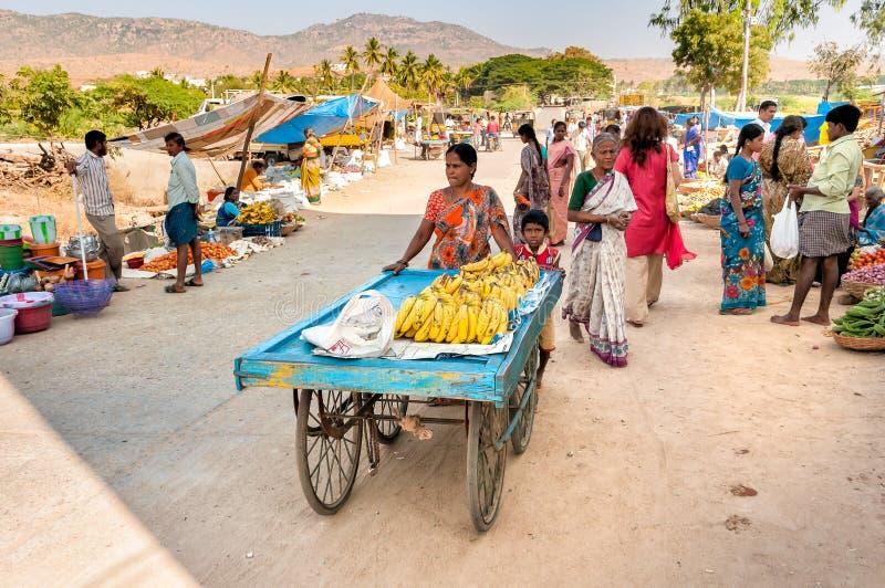 Moder och son som säljer bananer på gatamarknaden av Puttaparthi, Indien royaltyfria bilder