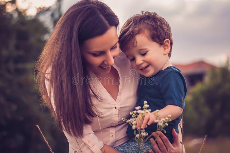 Moder och son som ser blommor royaltyfri fotografi