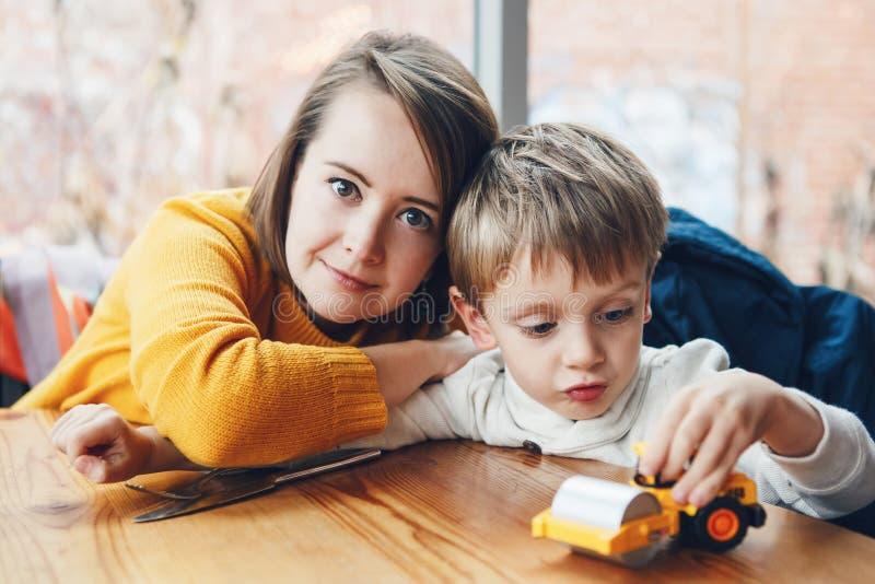 Moder och son som sitter i restaurangkafé på tabellen som ler att spela med leksakbilen royaltyfria foton