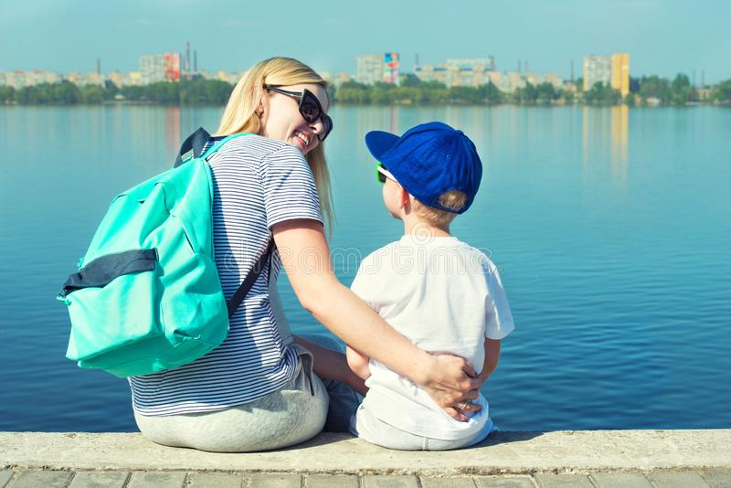 Moder och son som sitter på promenaden och blicken på floden arkivfoto