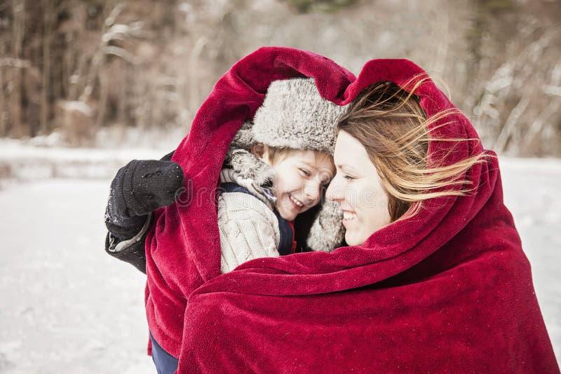 Moder och son som smyga sig under filten royaltyfri fotografi