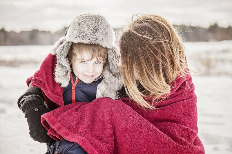Moder och son som smyga sig under filten fotografering för bildbyråer