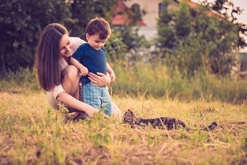 Moder och son som spelar med katten fotografering för bildbyråer