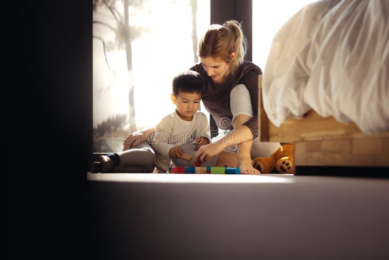 Moder och son som spelar med leksaker i sovrum royaltyfria foton