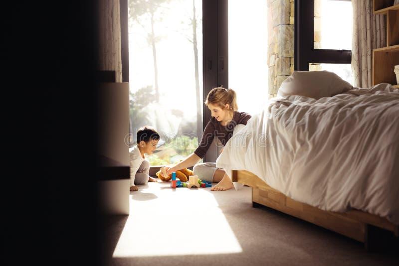 Moder och son som spelar med träkvarter arkivfoton