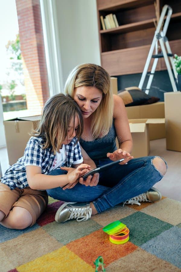 Moder och son som spelar minnestavlan arkivbilder