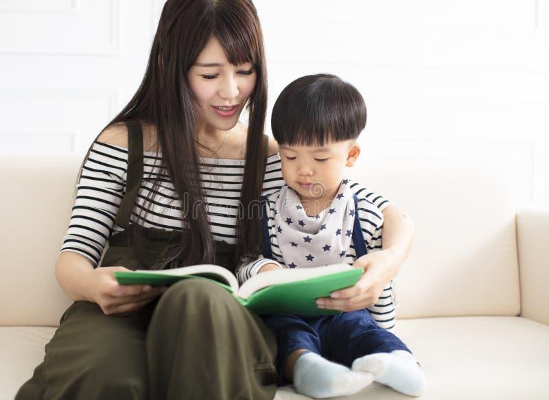 Moder och son som studerar på soffan arkivbilder