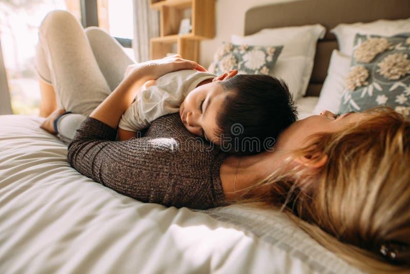Moder och son som tillsammans sover i säng royaltyfri bild