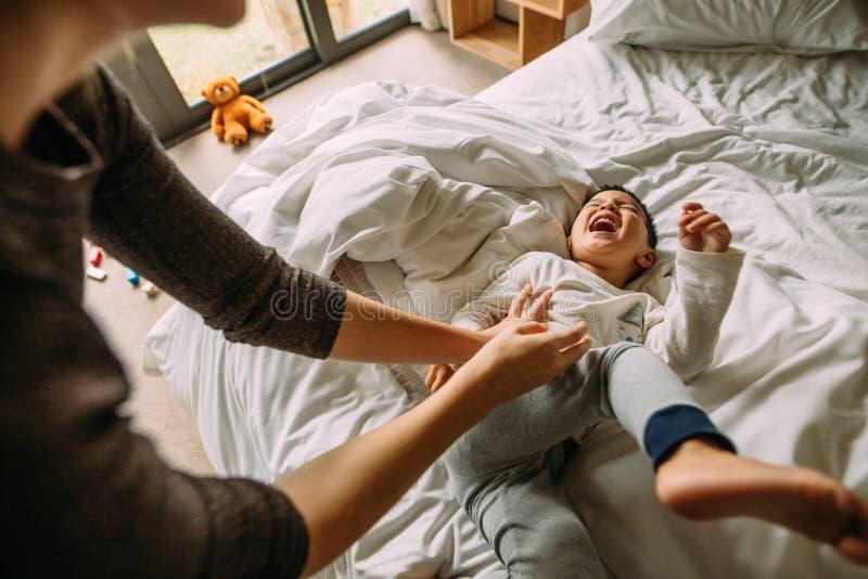 Moder och son som tillsammans spelar på säng royaltyfria bilder