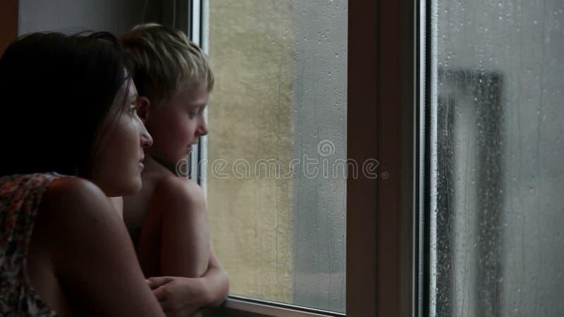 Moder och son som väntar på någon för att komma se ut fönstret under regnet