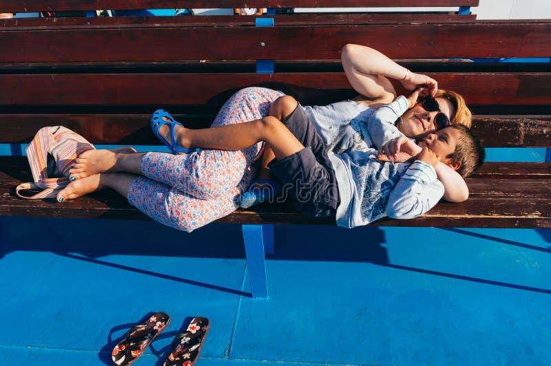 Moder och son som vilar på en bänk arkivbild