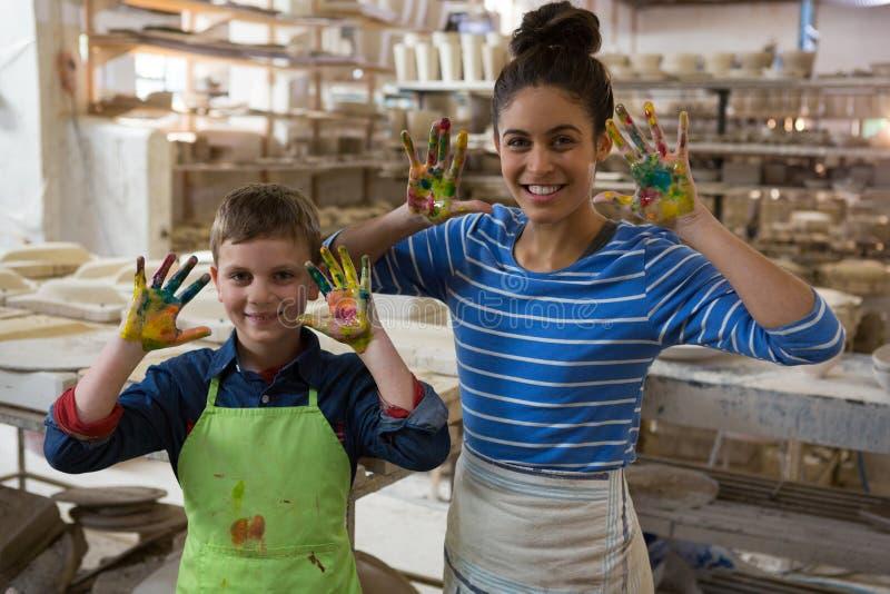 Moder och son som visar färgrik målarfärg på deras händer arkivbilder