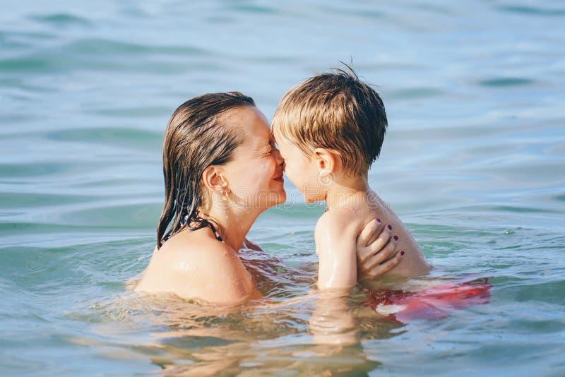 Moder- och sonbarnpojke som spelar att krama i vattendykning i havshavet arkivfoton
