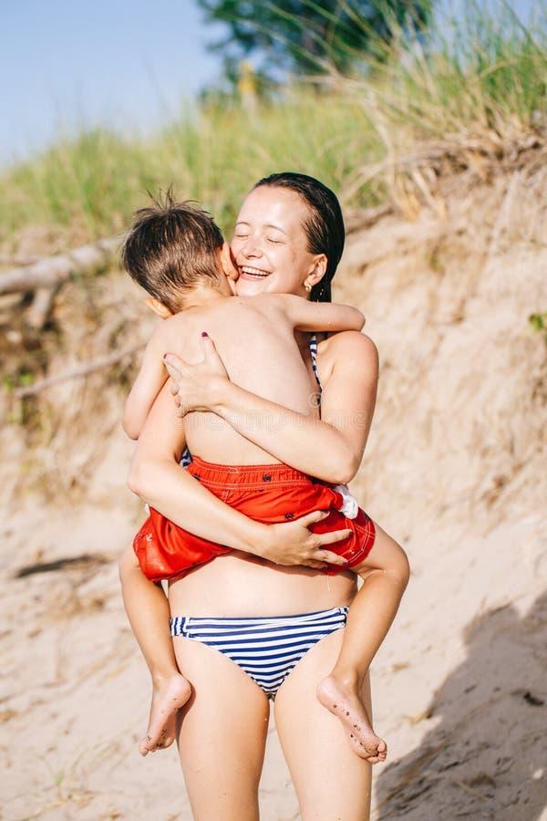Moder- och sonbarnpojke som spelar att krama på sandstranden nära havshavet arkivbilder