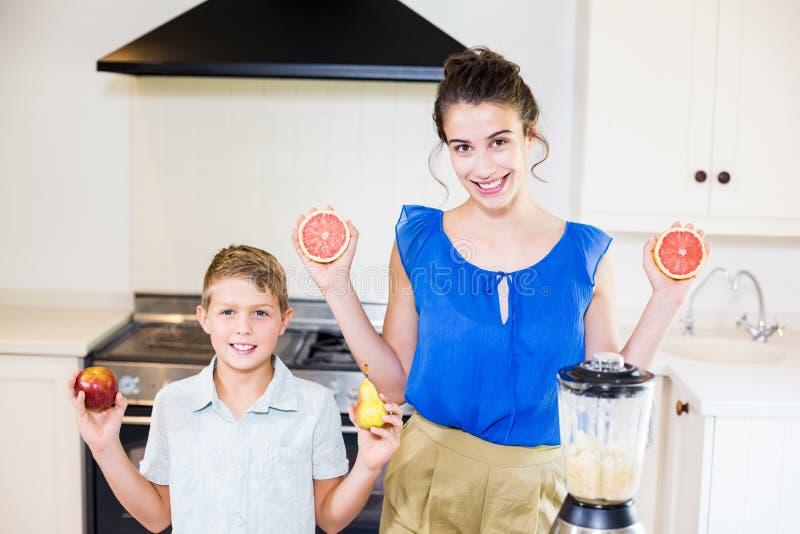 Moder- och soninnehavet bär frukt i kök royaltyfri foto