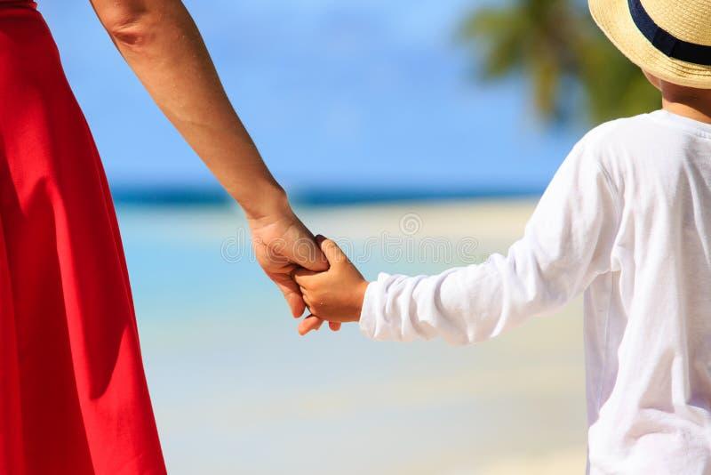 Moder- och soninnehavhänder på stranden royaltyfri fotografi