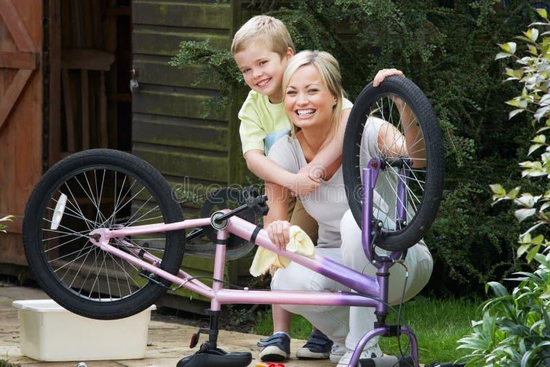 Moder- och sonlokalvård cyklar tillsammans royaltyfri bild