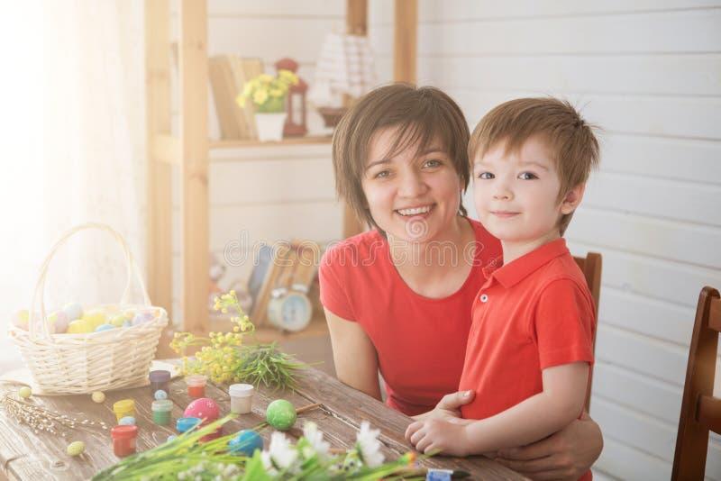 Moder- och sonmålarfärgägg Familj som sitter i ett kök easter förbereda sig Lyckliga easter för familjmamma- och barnsonmålarfärg royaltyfri fotografi