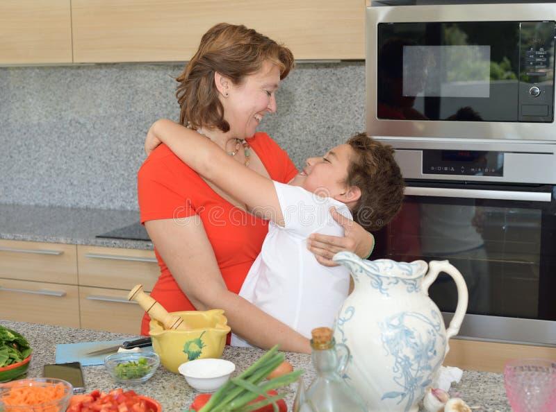 Moder- och sonomfamning, medan förbereda lunch royaltyfria foton