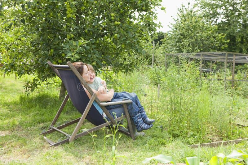 Moder- och sonsammanträde på solstol i odlingslott royaltyfria foton