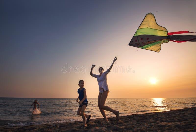 Moder- och sonspring med draken på stranden fotografering för bildbyråer