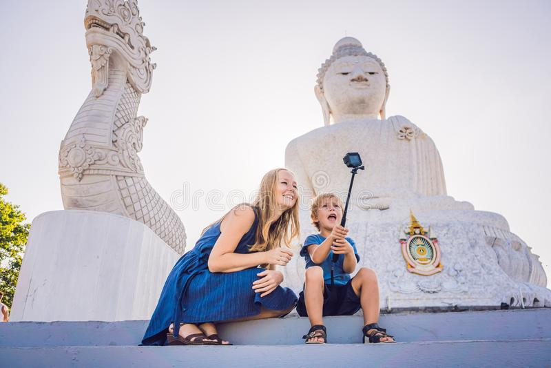 Moder- och sonturister på den stora Buddhastatyn Byggdes på en hög bergstopp av Phuket Thailand kan ses från ett avstånd royaltyfria bilder