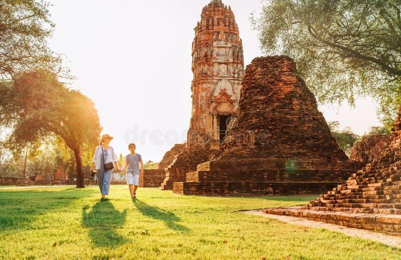 Moder- och sonturister som går handen - i - hand i atcient Wat Chaiwatthanaram Buddhist tempelruines i den heliga staden Ayutthay arkivfoton