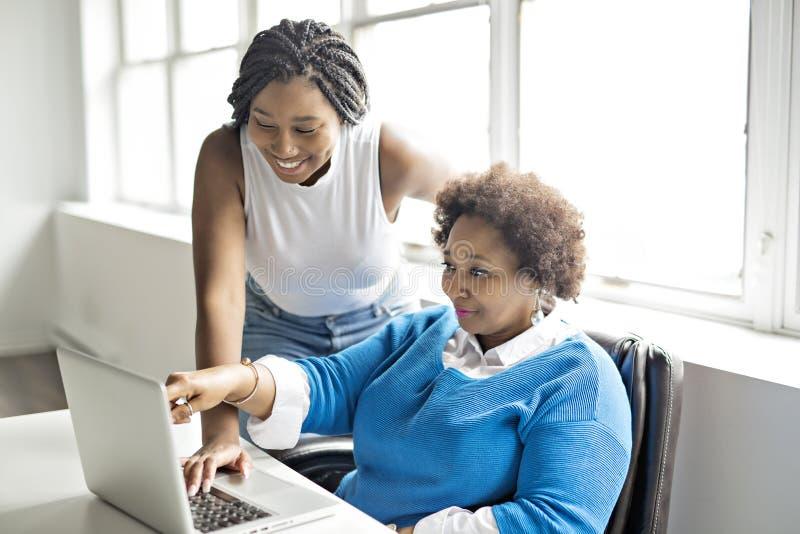 Moder och tonårs- dotter med bärbara datorn tillsammans arkivfoton