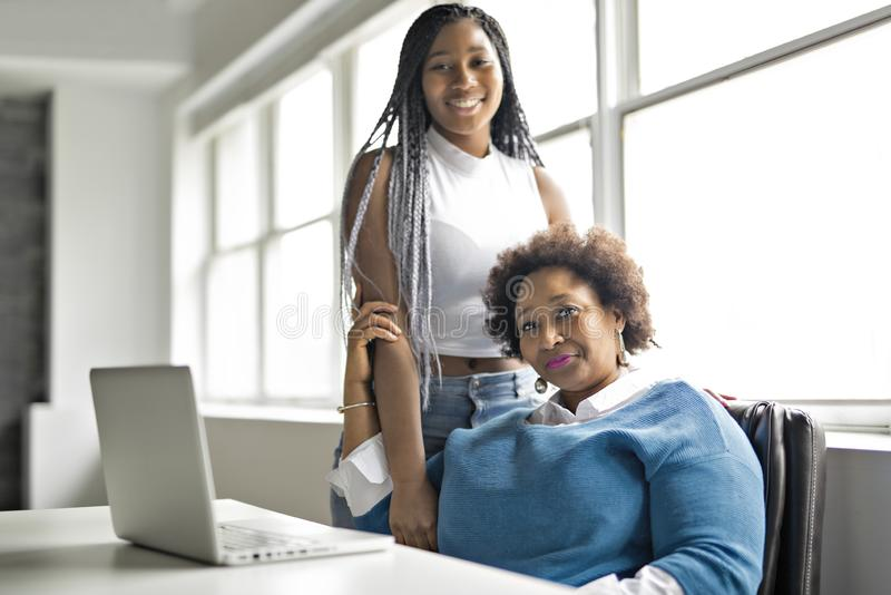 Moder och tonårs- dotter med bärbara datorn tillsammans arkivbild