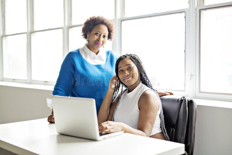 Moder och tonårs- dotter med bärbara datorn tillsammans royaltyfri bild