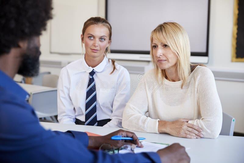 Moder och tonårs- dotter som har diskussion med för At High School för manlig lärare afton föräldrar arkivbilder