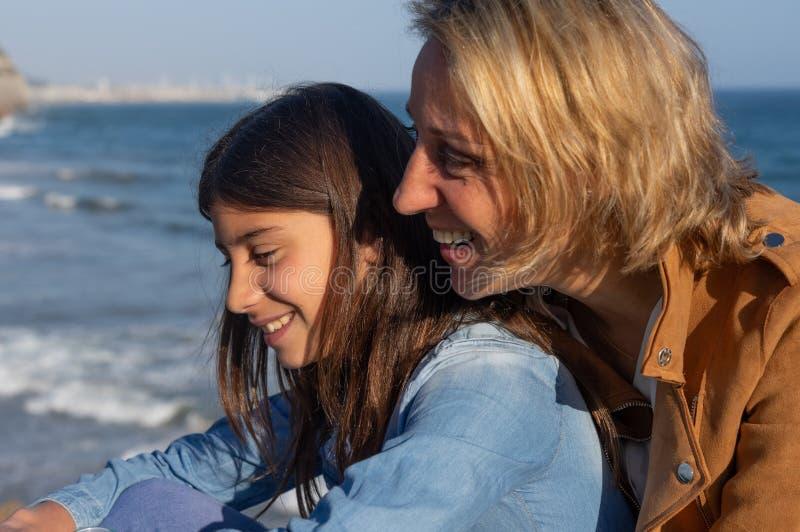 Moder och tonårs- dotter som skrattar vid medelhavet royaltyfri fotografi