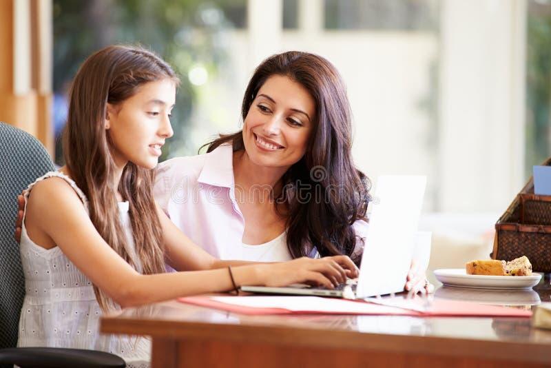 Moder och tonårs- dotter som tillsammans ser bärbara datorn royaltyfria bilder