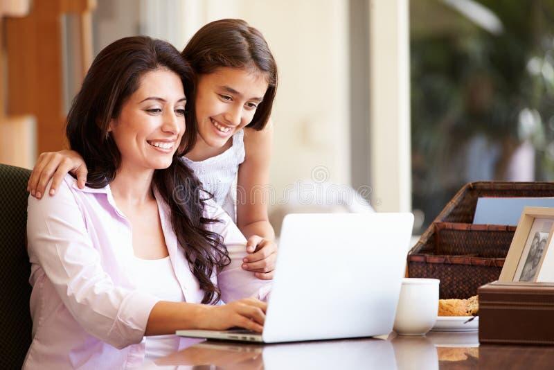 Moder och tonårs- dotter som tillsammans ser bärbara datorn fotografering för bildbyråer
