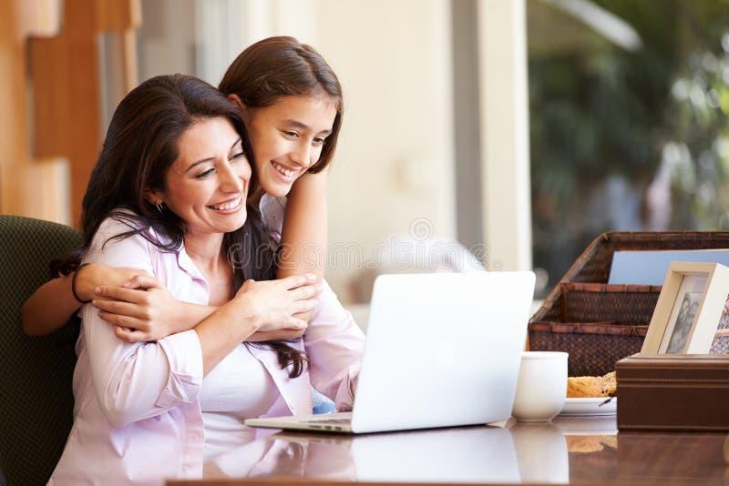 Moder och tonårs- dotter som tillsammans ser bärbara datorn arkivfoto