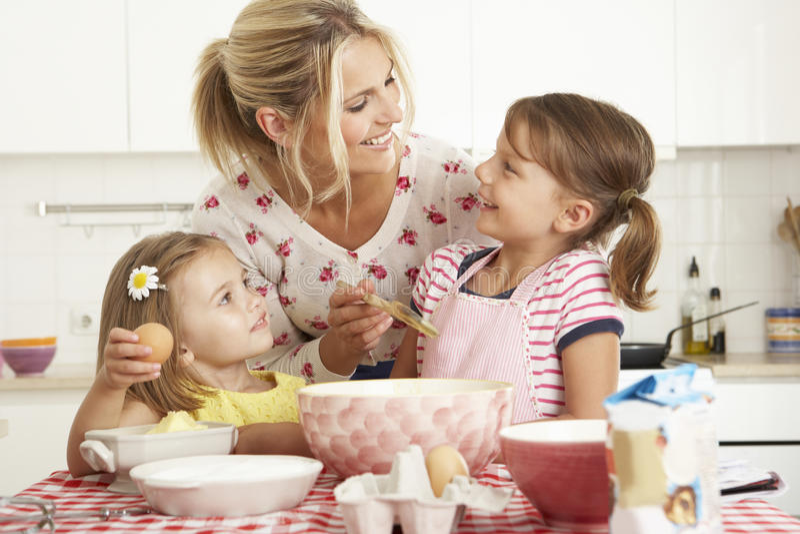 Moder och två flickor som bakar i kök fotografering för bildbyråer