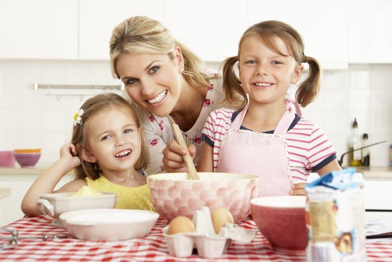 Moder och två flickor som bakar i kök arkivbild