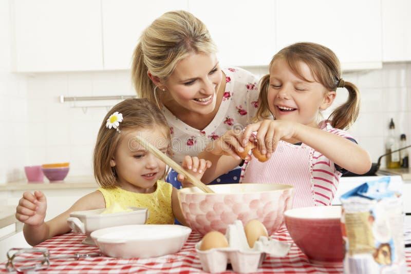 Moder och två flickor som bakar i kök royaltyfri fotografi
