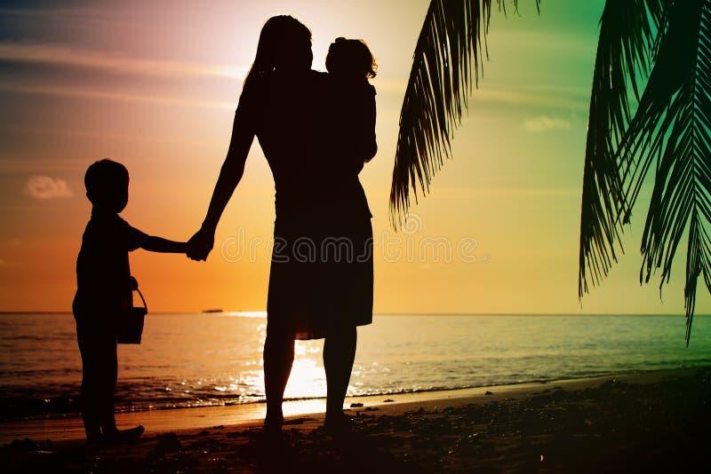 Moder och två ungar som går på stranden på solnedgången arkivbild