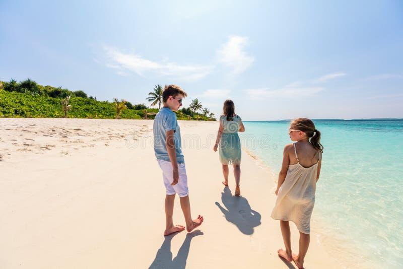 Moder och ungar på den tropiska stranden royaltyfri foto