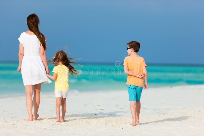 Moder och ungar på en tropisk strand fotografering för bildbyråer