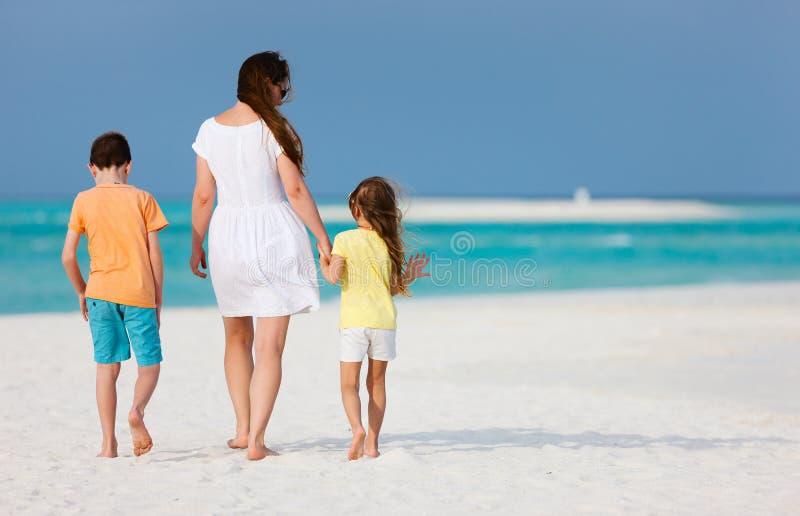 Moder och ungar på en tropisk strand royaltyfri bild