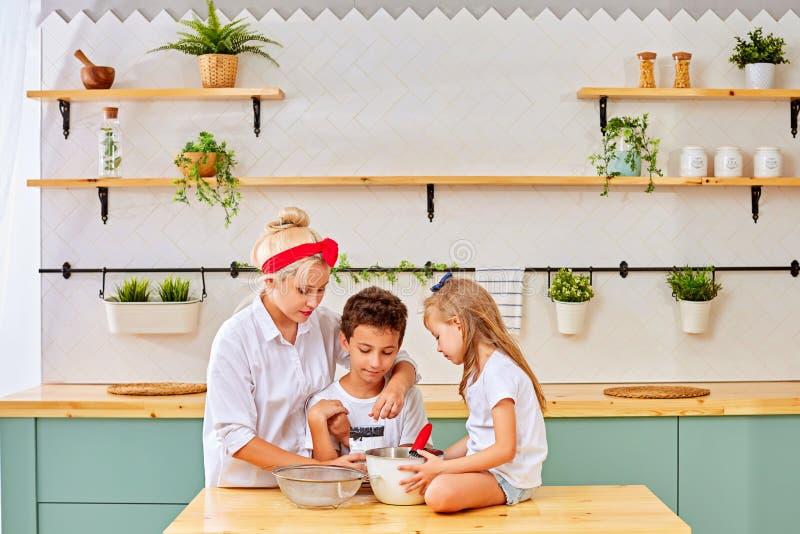 Moder och ungar som förbereder bakelse i kök royaltyfri fotografi