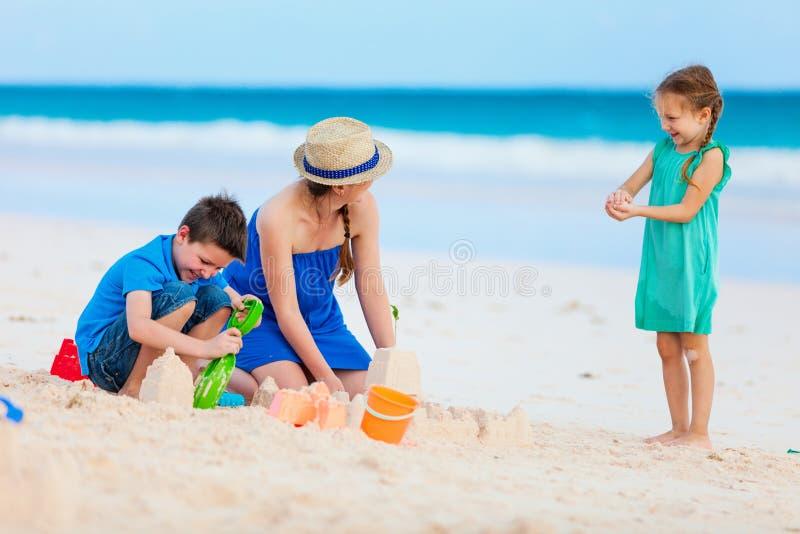 Moder och ungar som spelar på stranden royaltyfria bilder