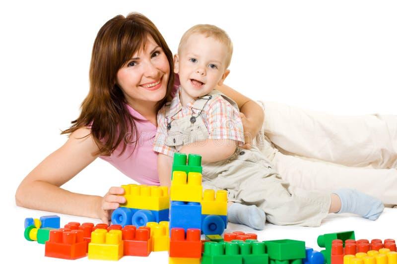 Moder och unge som spelar färgrika leksaker för byggnadskvarter, lycklig familj arkivbilder